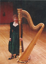 Janice Ortega onstage with a gold concert grand harp.