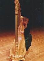 Janice Ortega on stage with a gold concert garnd harp.