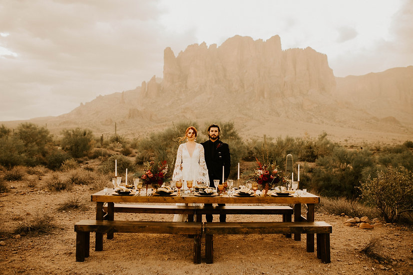 Bride and groom standing behind wooden farm table and benches