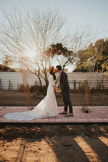 bride and groom kissing under a copper wedding arch