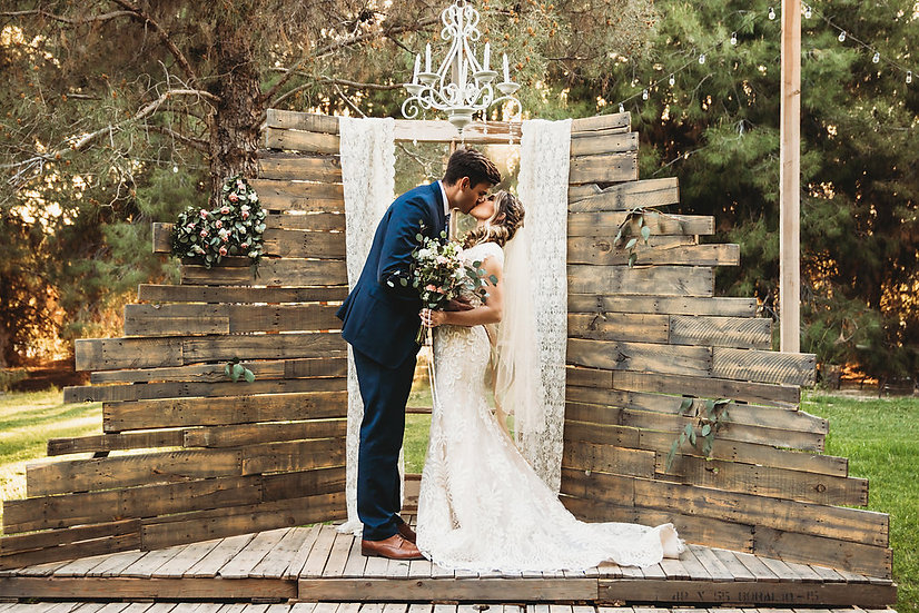 Bride and groom kissing in front of rustic wedding backdrop in the forrest