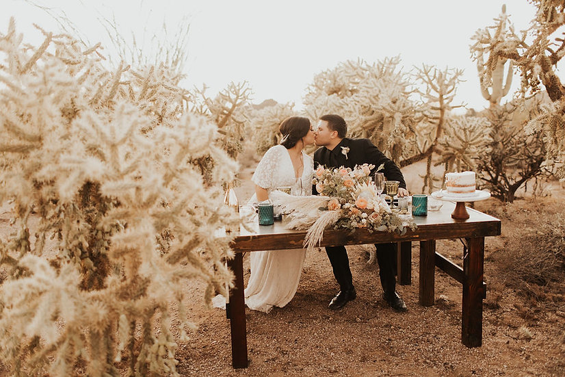 bride and groom sitting at a sweetheart table in the desert