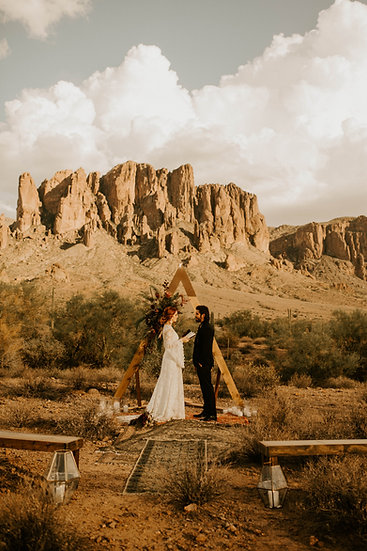 bride and groom in the desert eloping standing in front of a triangle arch