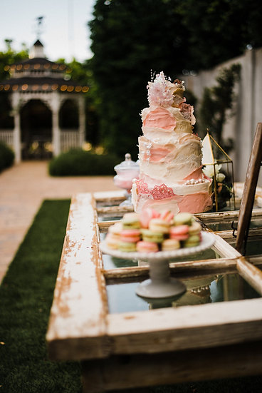 a vintage white french door table with wedding cake set on it