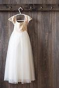 Wedding dress against barn wall.