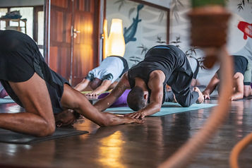Men doing yoga, extended puppy pose, in a yoga studio