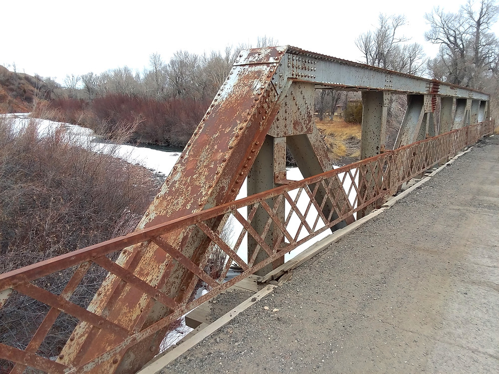 Old rusty bridge over river near small remote town of Dubois, Wyoming