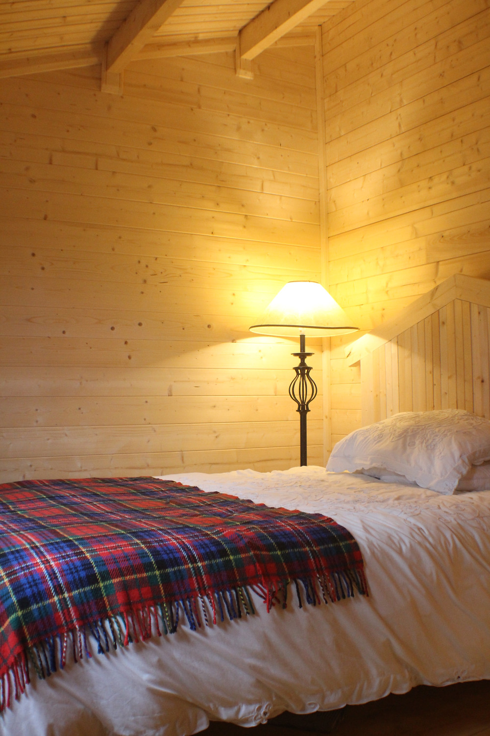 Log cabin bedroom with lamp, homemade bed and timber walls