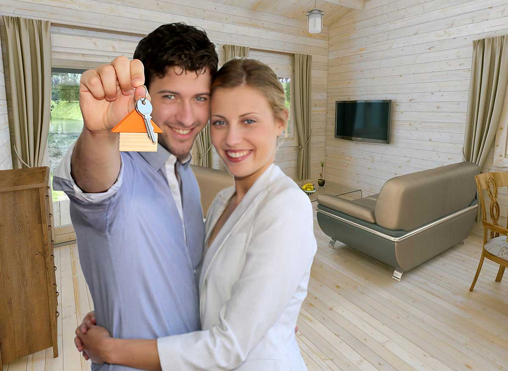 Couple holding keys to their log cabin