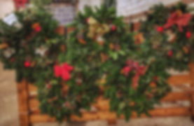 five christmas wreathes hung on a hurdle