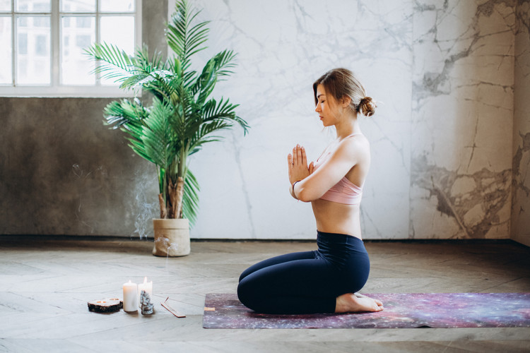 woman-meditating-with-candles-and-incens