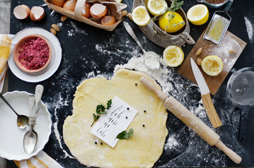 dough-and-flour-near-lemons-and-rolling-