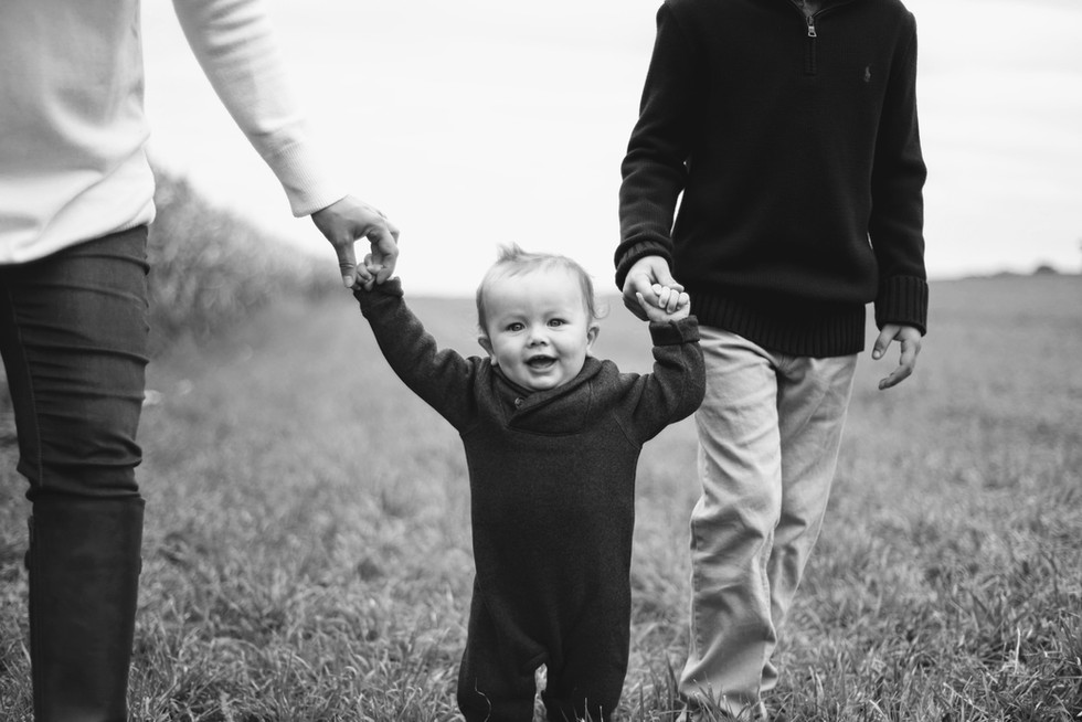 baby walking with mother and brother in outdoor natural light family photo portrait