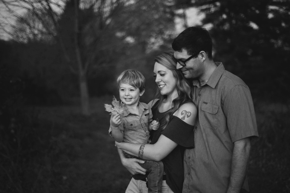 mother and father holding son in outdoor fall family portrait