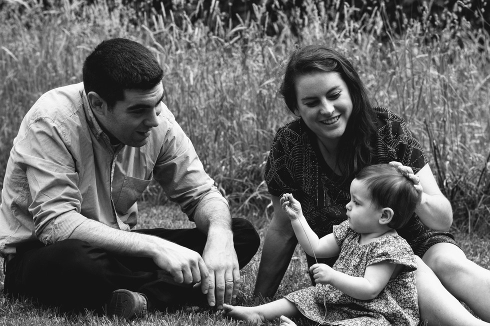 mom and dad with baby girl seated outdoors