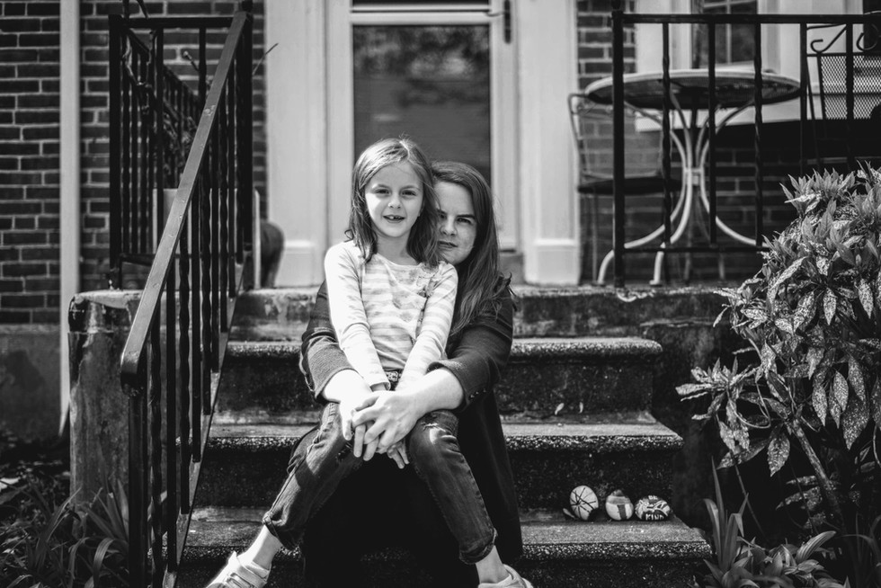 mother and daughter portrait on front steps holding hands loving embrace