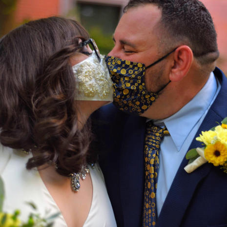 bride and groom kissing in pandemic masks at outdoor wedding