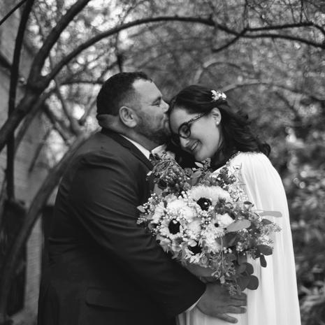 groom kissing bride on forehead pre ceremomy with flowers