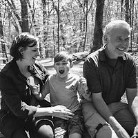 Mom, dad, son laughing in an outdoor documentary family photo session