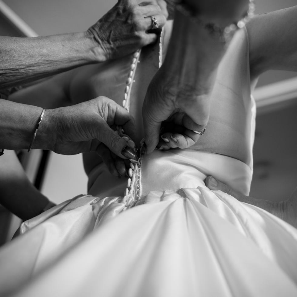 many hands buttoning bride's wedding dress black and white photo