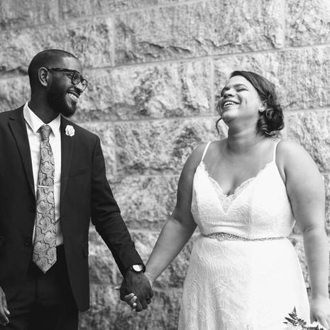 newly wedded couple holding hands laughing