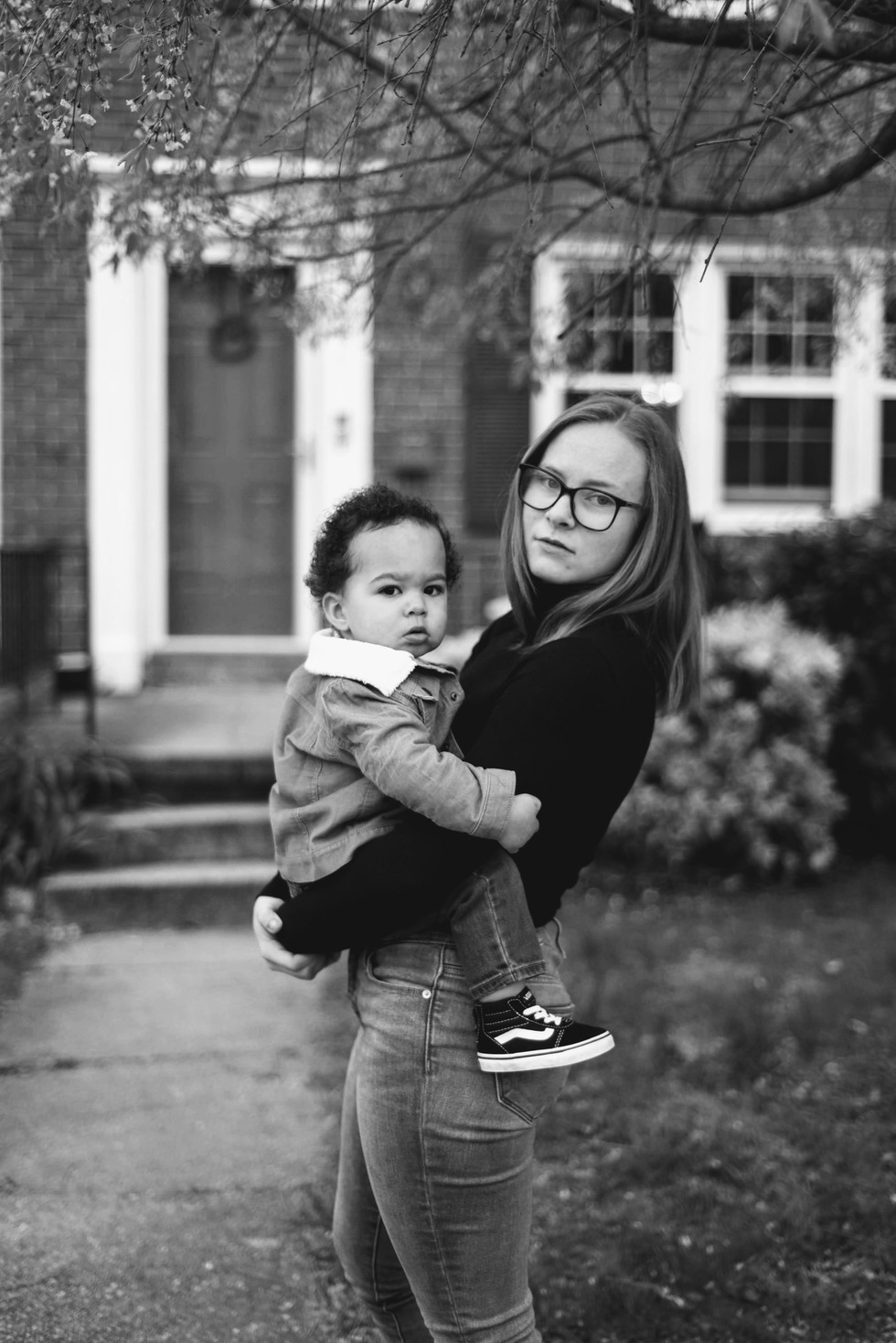 mom holding son in front of house