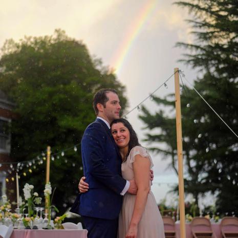 newly wedded couple embracing under rainbow at wedding