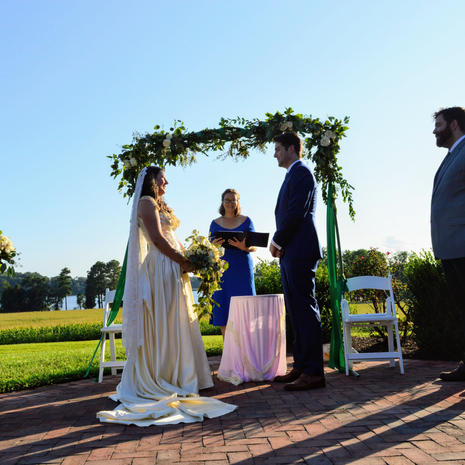 couple at outdoor wedding venue under flower arch reciting vows candid