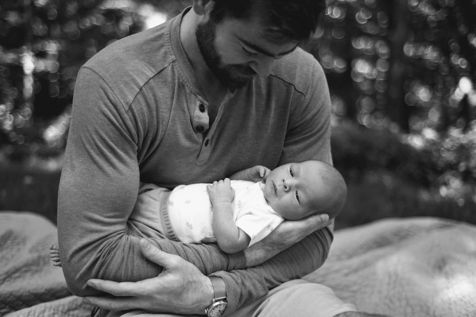 dad holding newborn son outdoor photo portrait