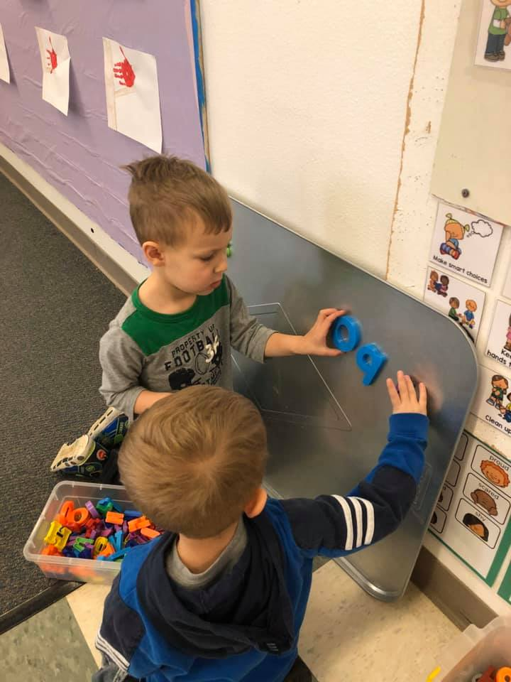 Two children spelling words with magnetic letters
