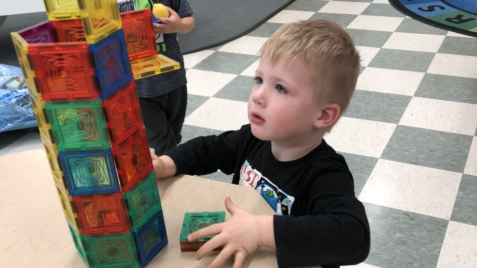 Young child playing with magnetic squares