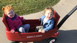 Two toddlers being pulled in a wagon