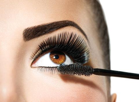 Mascara applying. Long Lashes closeup. Mascara Brush. Eyelashes extensions. Makeup for Brown Eyes. E