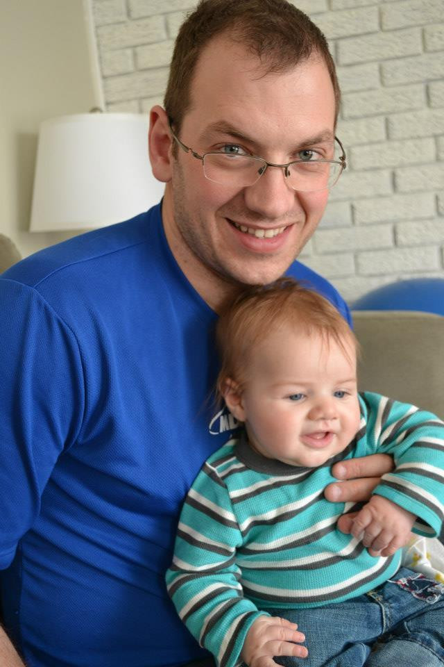 Toby James, co-owner of Cat's Cove Communications holding young son, Alex.