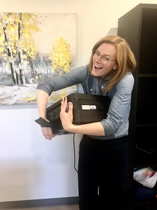 Cat's Cove Communications' Sasha holding her new printer at the Cat's Cove Communications Office
