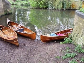 Three Men in Wooden Canoes