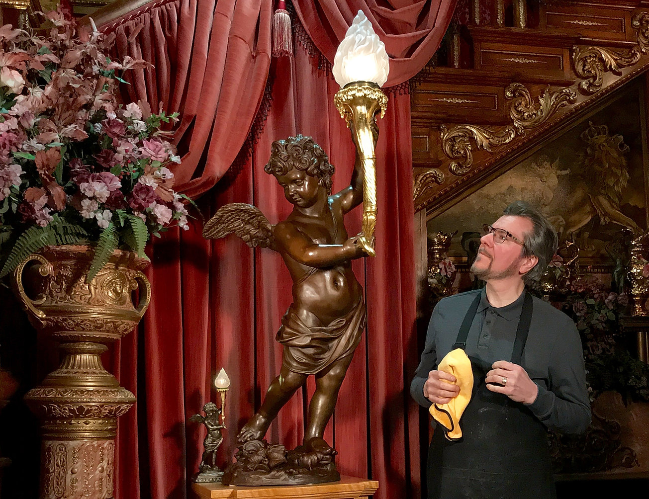 Titanic sculptor Alan St George and his finished full-sized bronze cherub lamp replica with 24 karat gold torch. The tiny scale model on the left was completed 8 months earlier to prepare for the large sculpture.