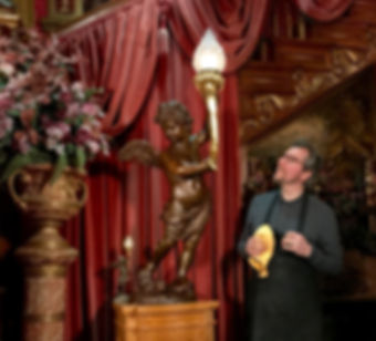 Titanic sculptor Alan St. George surveys his full-sized bronze of the Grand Staircase cherub lamp with gold-leafed torch, standing next to his smallest cherub lamp recreation