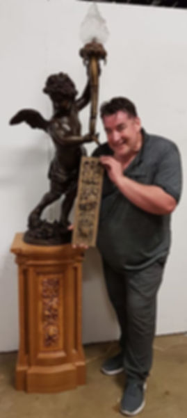 Titanic collector John White and owner of White Star Memories holds up an original newel carving from RMS Olympic in front of the historically accurate bronze replica of Titanic's famous cherub lamp by Alan St. George.
