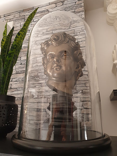 Titanic cherub head by sculptor Alan St George displayed under glass