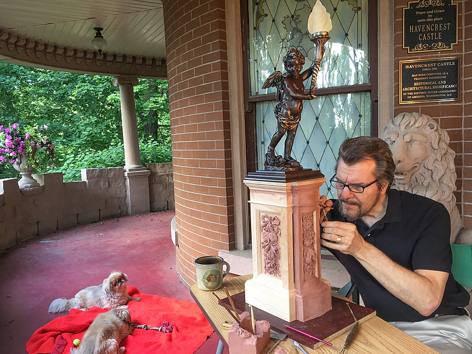 Titanic sculptor Alan St George works on his Grand Staircase Cherub pedestal. Carving out a great day with some of his favorite things: My dogs, my front porch, coffee, and making a new sculpture.