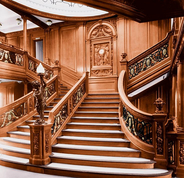 Titanic Grand Staircase with clock, cherub lamp, and balustrades.