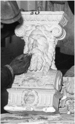 Titanic's first-class dining room Neptune head being resotred in 1929 on her nearly identical twin sister ship the RMS Olympic.