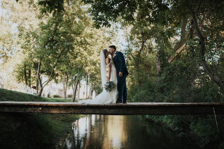 bride-groom-kiss-bridge-blue-heron-barn