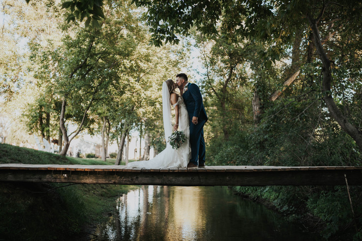 bride-groom-kiss-bridge-blue-heron-barn