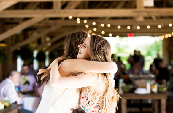 bride-friend-hugging-blue-heron-barn.jpeg