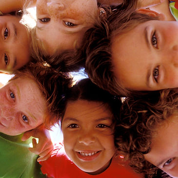 Jeunes enfants souriants qui joignent leur tête ensemble. Vue d'en bas.