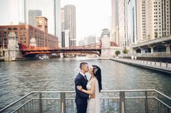 Elegant wedding couple standing near riv