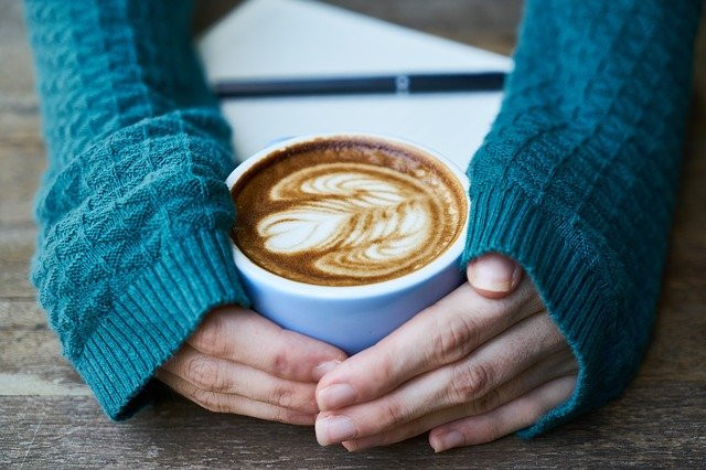 A woman hugging a cup of coffee with a heart in the milk at the top.