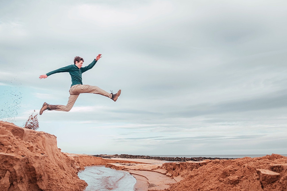 A man leaping over a river on the beach
